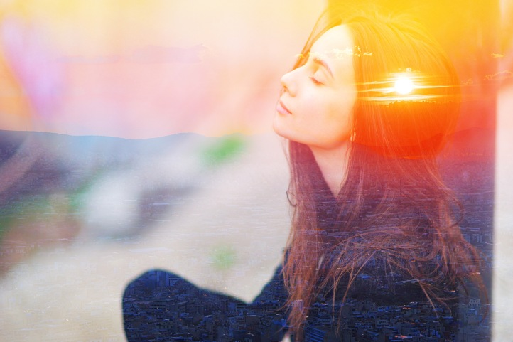 Double multiply exposure portrait of a dreamy cute woman meditating outdoors with eyes closed, combined with photograph of nature, sunrise or sunset. closeup. Psychology power of mind concept.